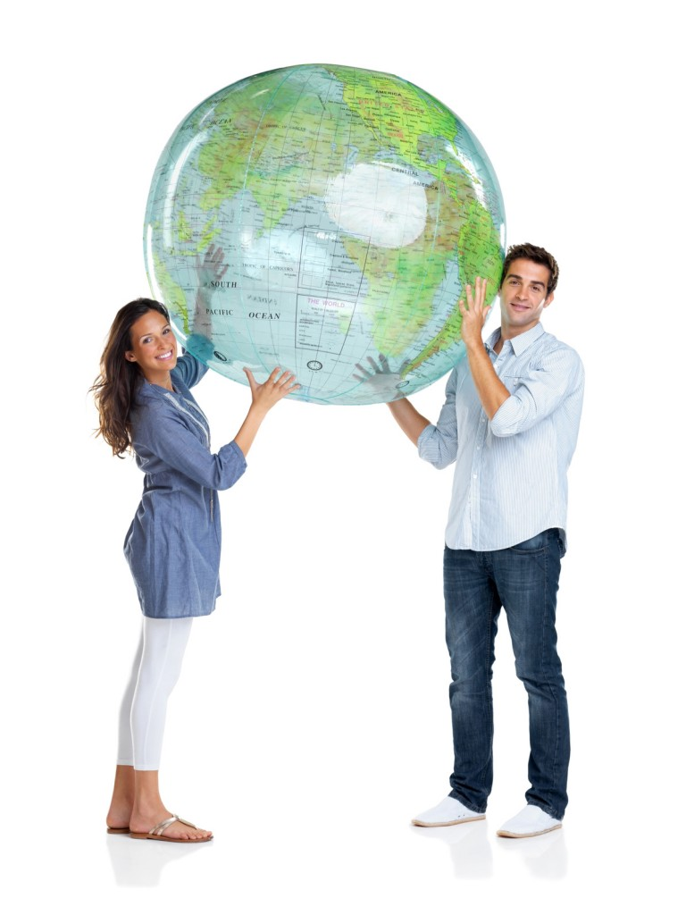 Portrait of a beautiful young couple holding a globe above head over white background