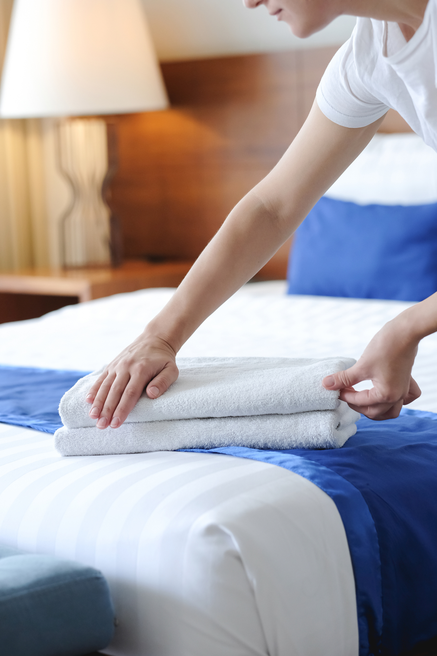 Hands of hotel maid bringing fresh towels to the hotel room