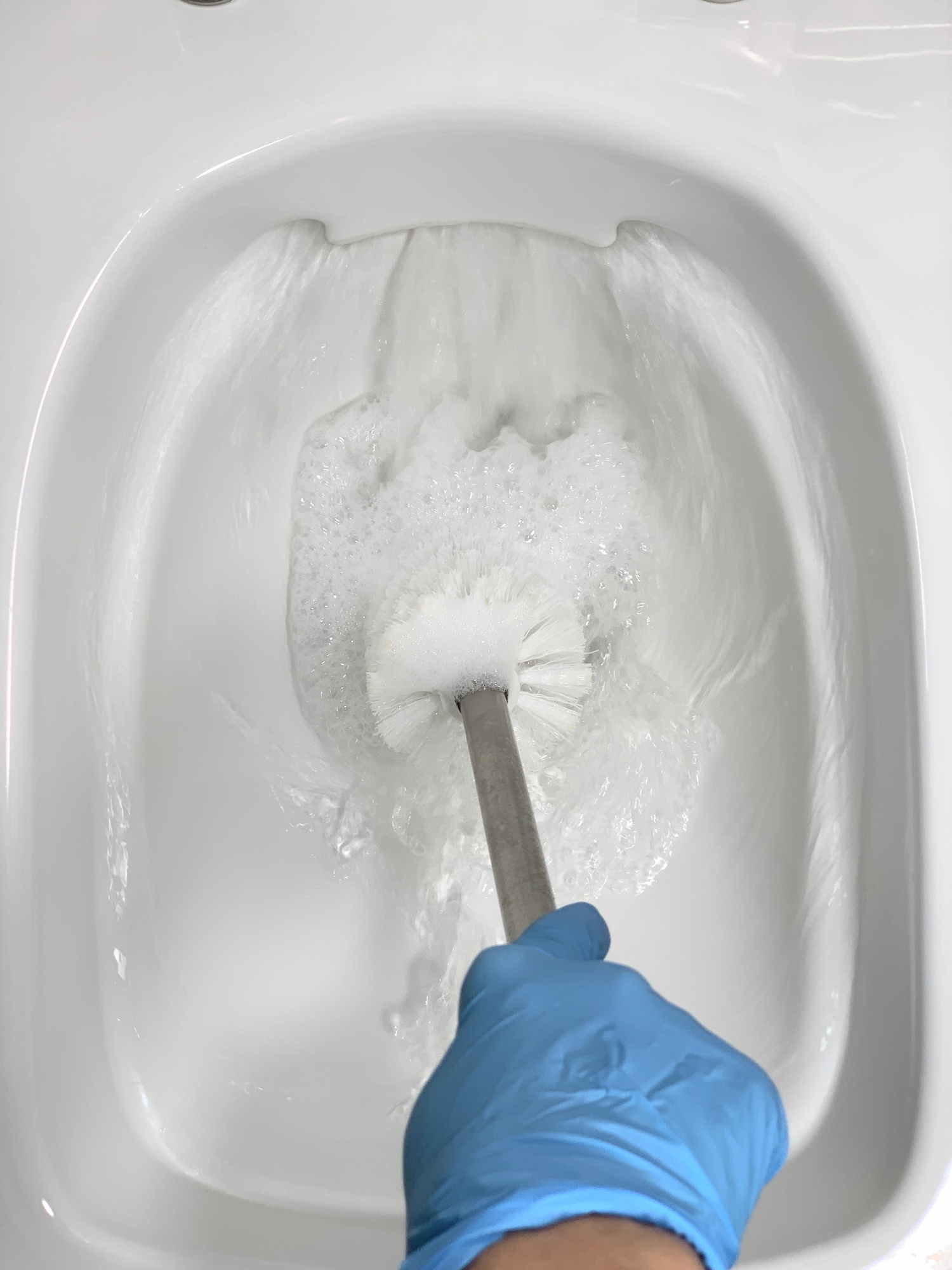 A man in gloves cleans the toilet with a brush.