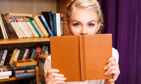 Young beautiful blonde student girl with book