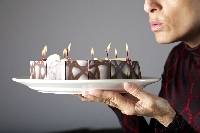 blowing out small candles on cake