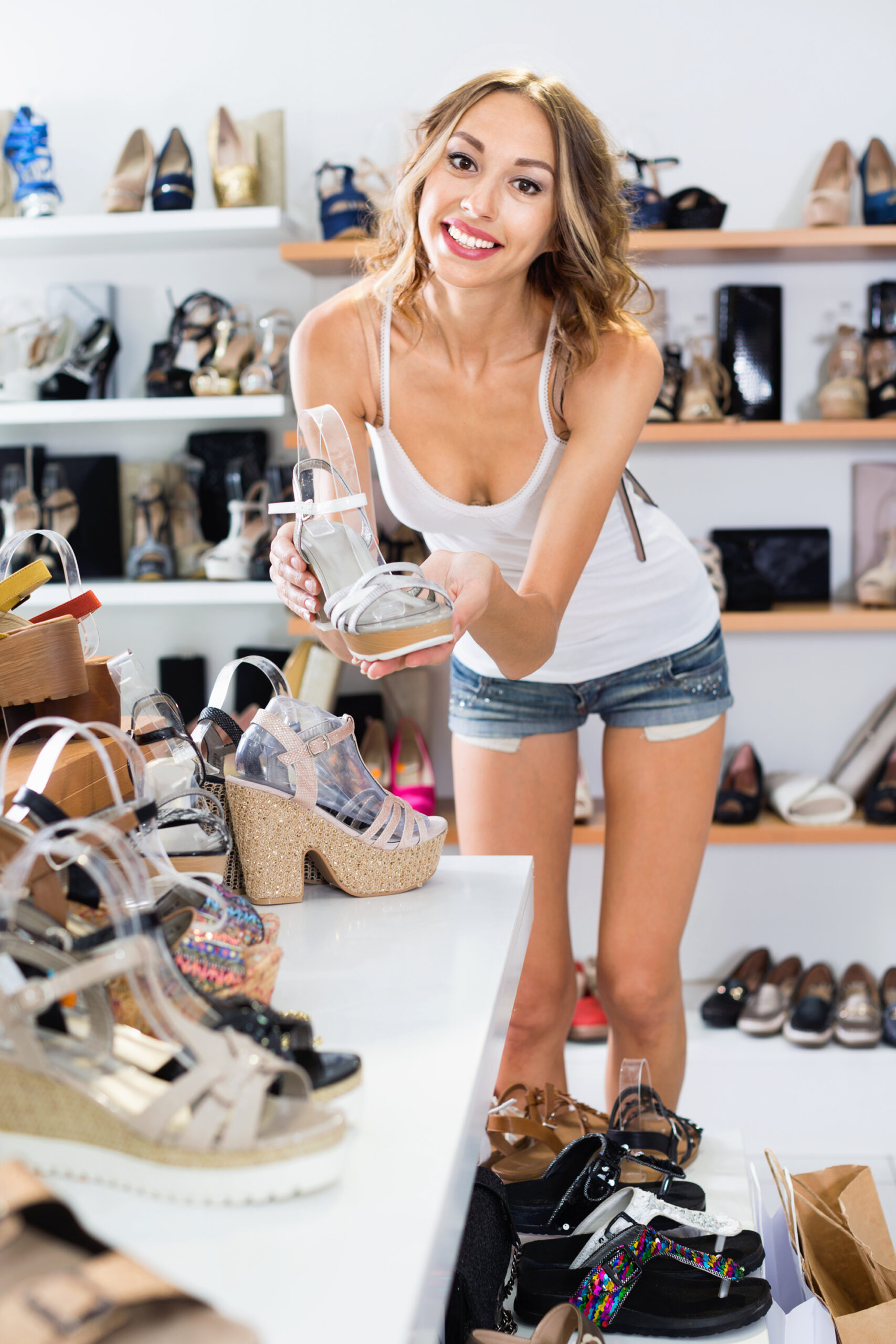 Girl is choosing ballet shoes in shoes shop