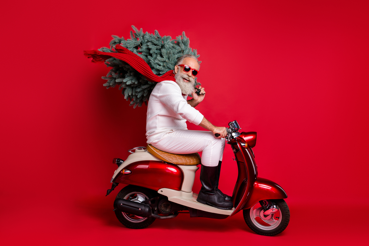 Full size profile side photo of cheerful pensioner on motorcycle carry fir tree travel hurry to christmas time wear sweater pants isolated, over red background