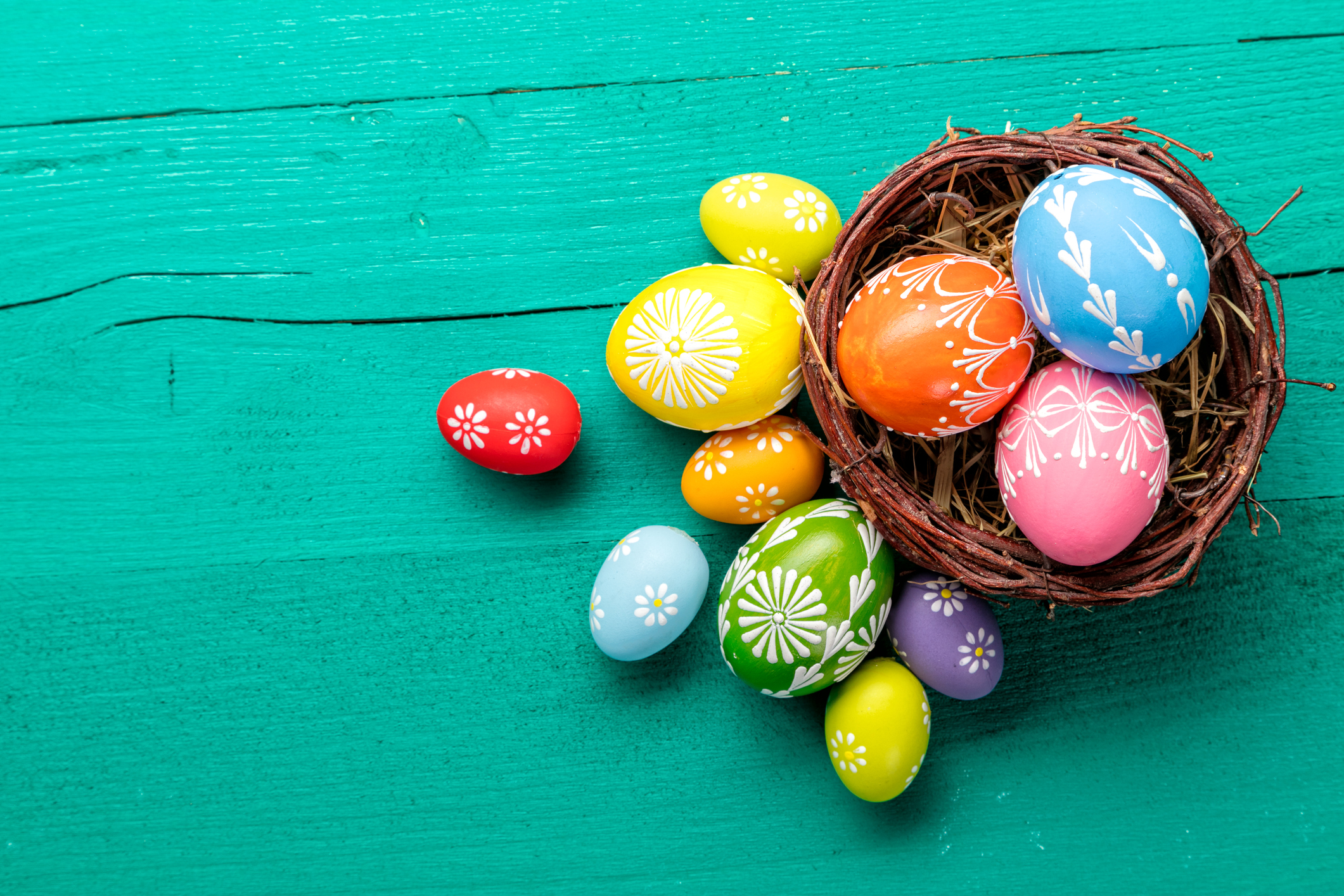 Easter eggs in basket placed on wooden planks