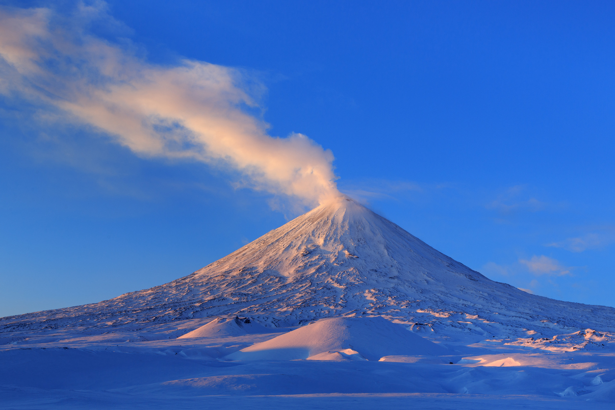 Beautiful winter volcanic landscape of Kamchatka Peninsula: view of eruption active Klyuchevskoy Volcano at sunrise. Eurasia, Russia, Far East, Kamchatka Region, Klyuchevskaya Group of Volcanoes.
