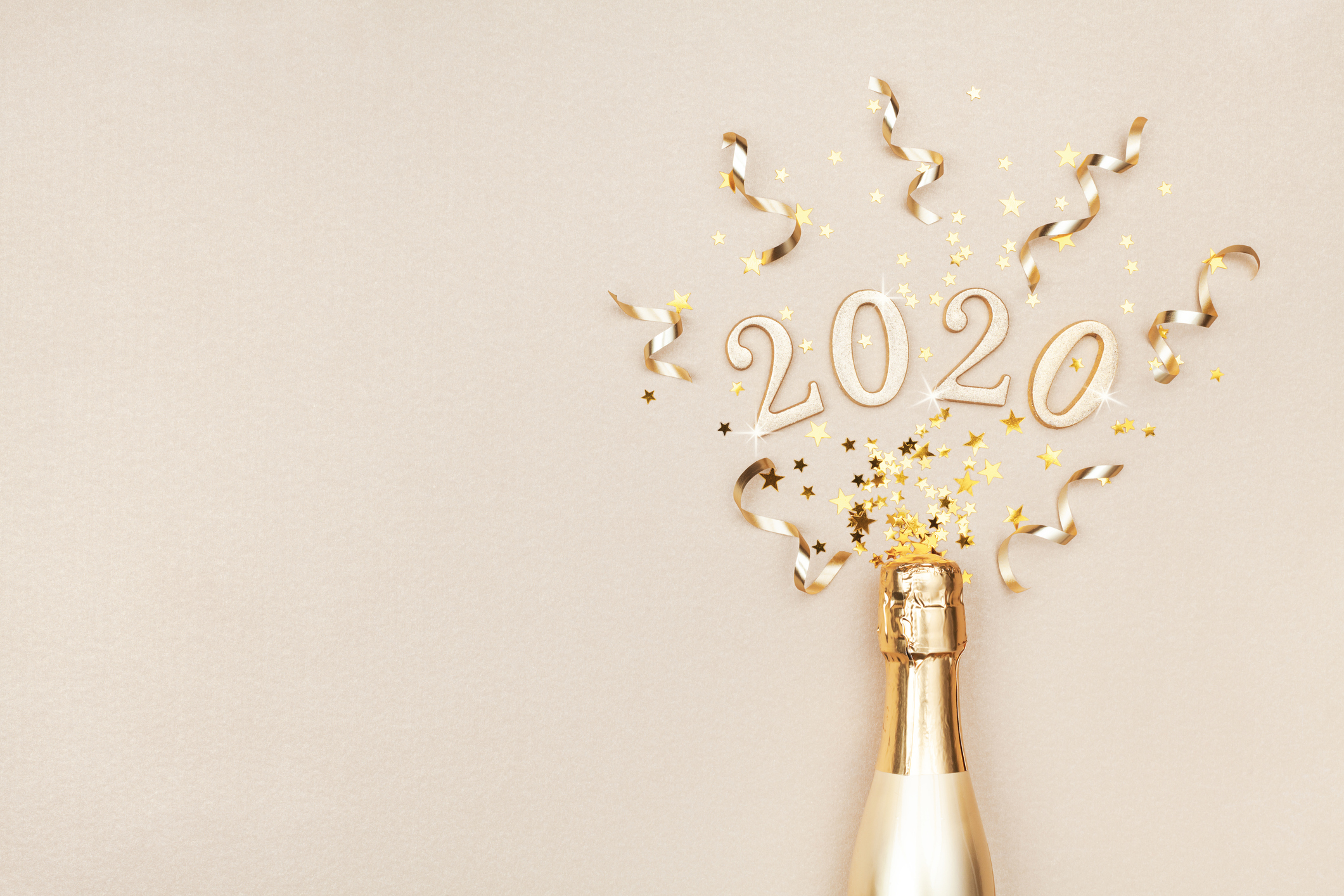 Creative Christmas and New Year flat lay composition with golden champagne bottle, party streamers, confetti stars and 2020 numbers.