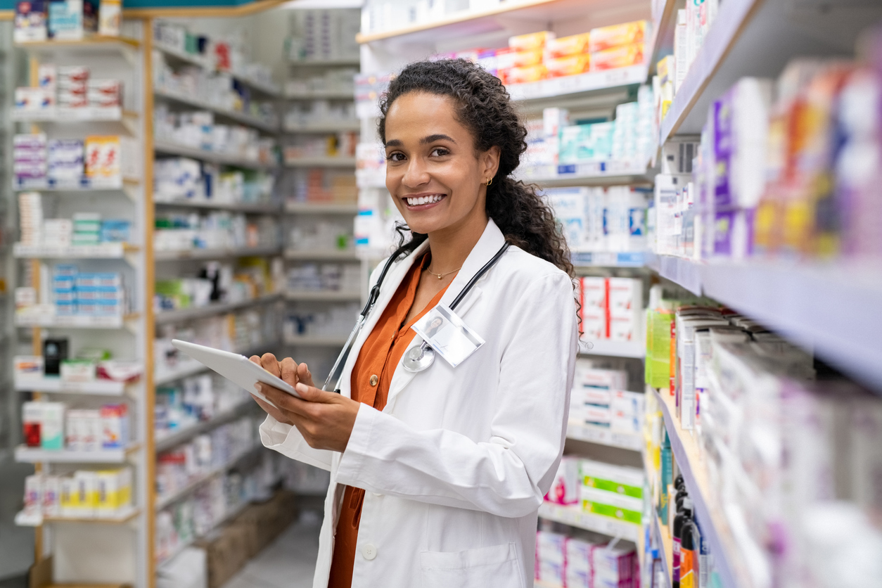 Young mixed race pharmacist using digital tablet