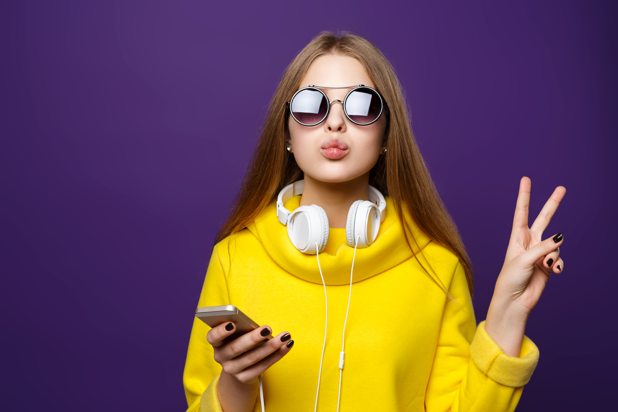 Portrait young girl teenager with earphones and phone, in a yellow sweater, isolate on a violet background.