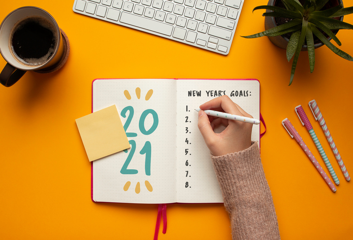 Woman writing goals in a 2021 new year notebook