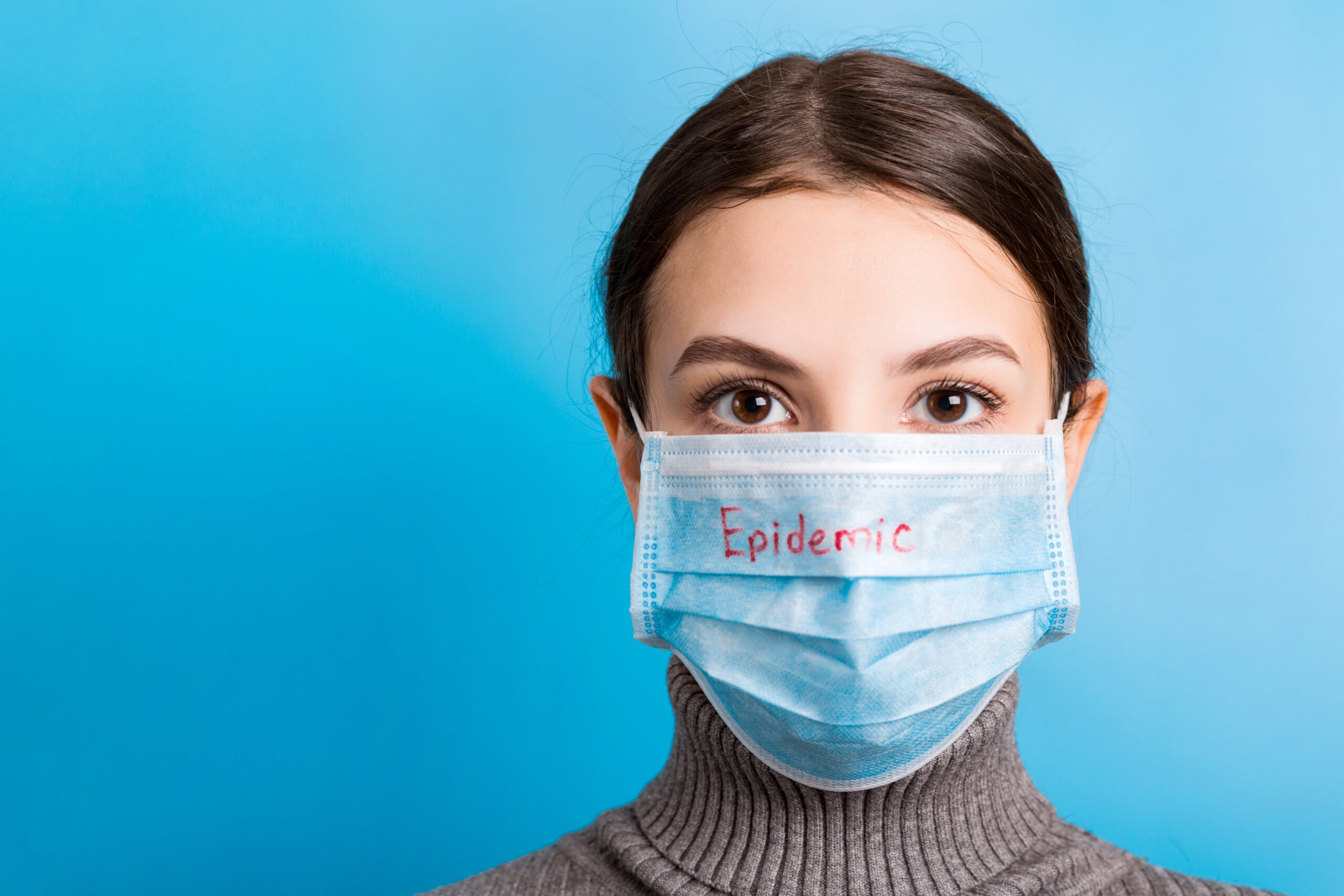 Portrait of young woman wearing medical mask with epidemic word at blue background. Protect your health. Coronavirus concept