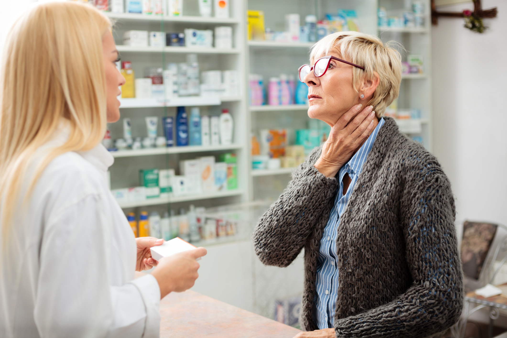 Tired, ill mature woman holding her throat and explaining problems to a beautiful young female pharmacist. Thyroid gland problems