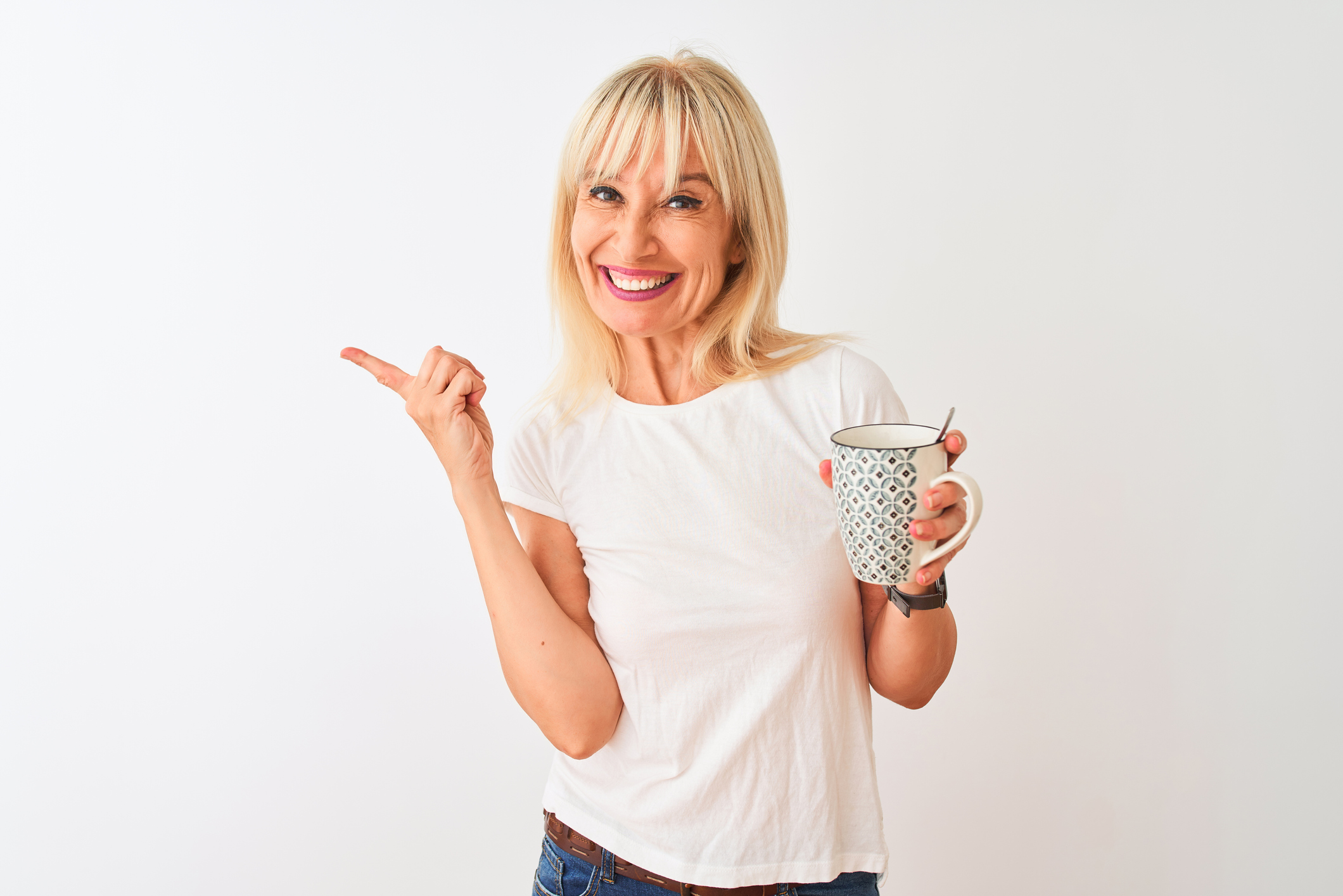 Middle age woman drinking cup of coffee standing over isolated white background very happy pointing with hand and finger to the side