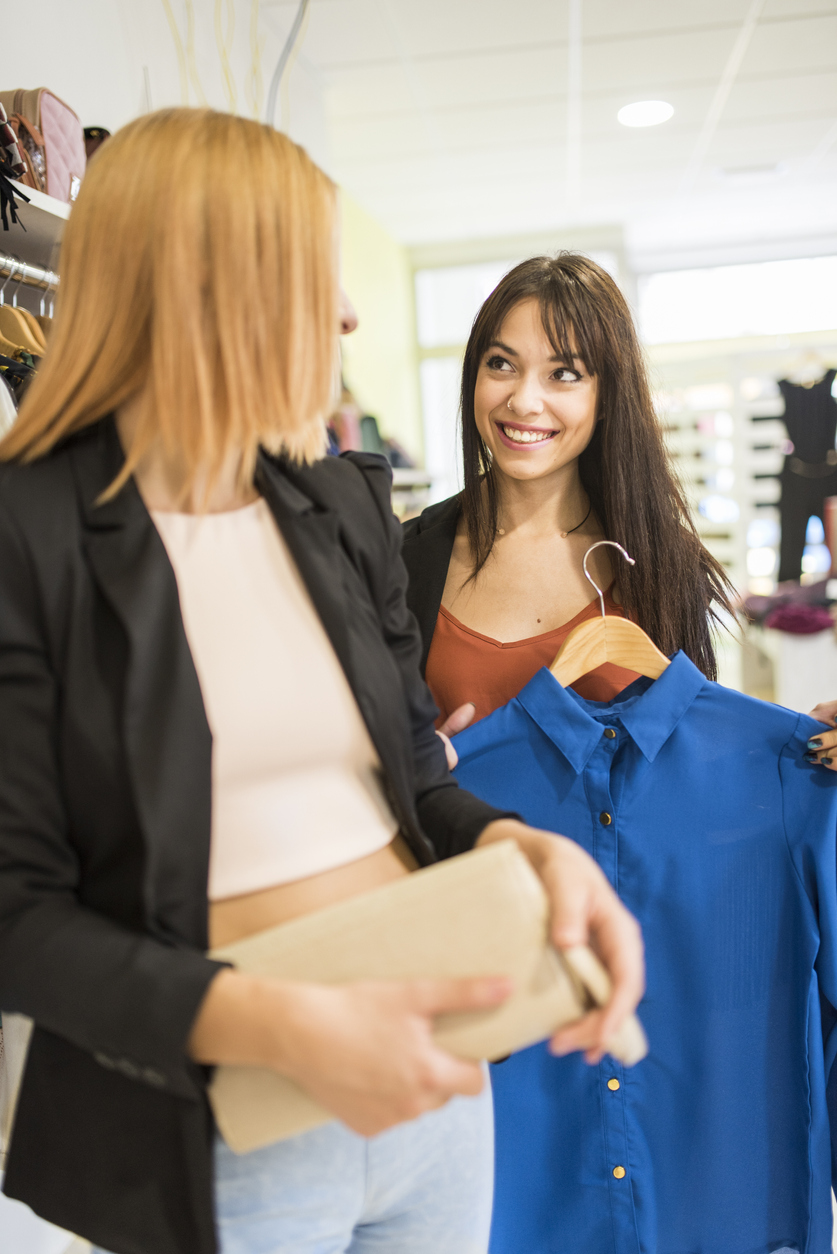 Two friends shopping clothes in fashion store