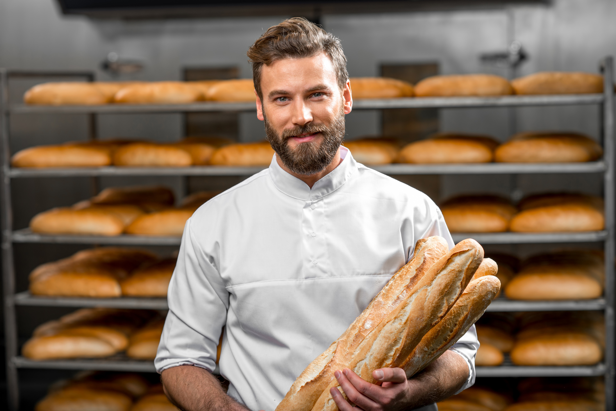 Baker holding baguettes at the manufacturing