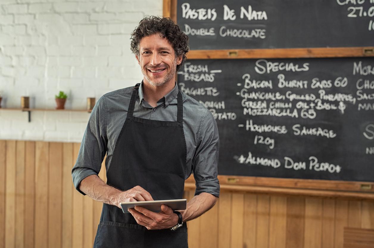 Waiter holding digital tablet at cafeteria