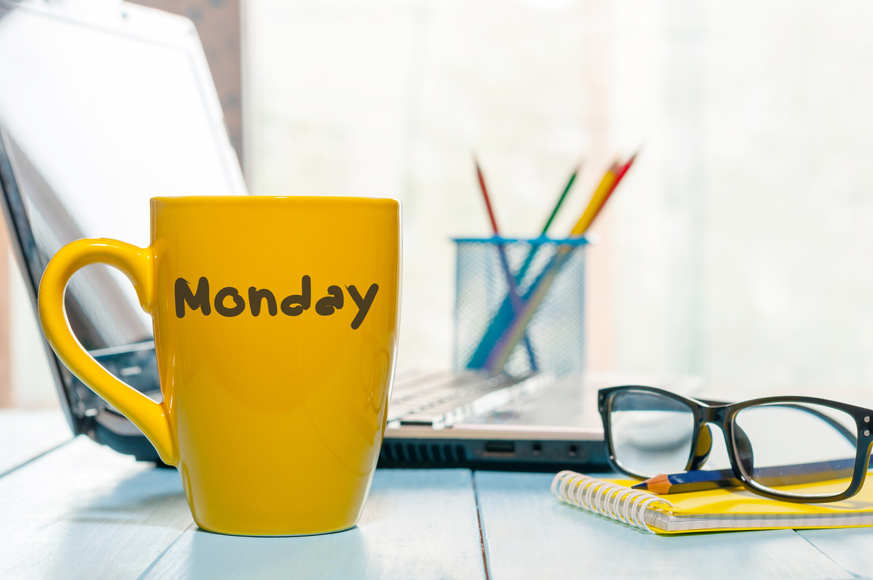 Monday written on yellow coffee or tea cup at wooden boards table, workplace, office sunlight morning background
