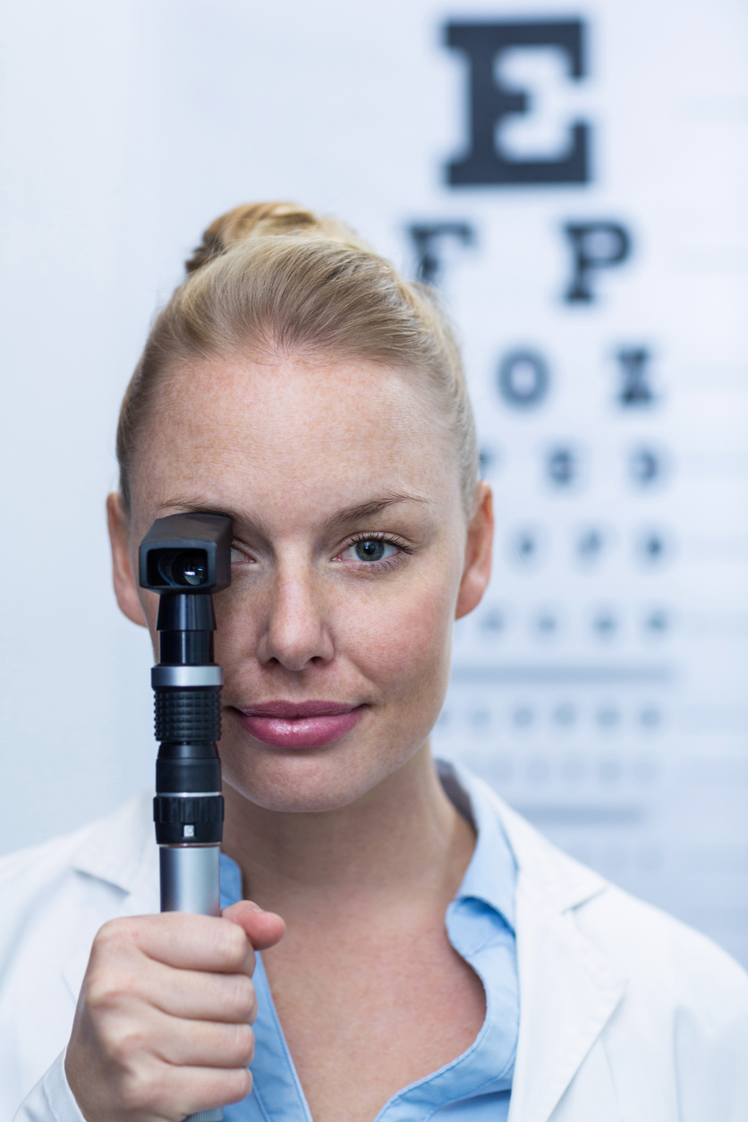 Female optometrist looking through ophthalmoscope