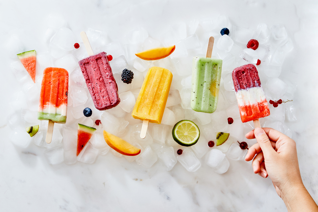 A woman's hand holds an ice cream popsicle against a background of ice cubes with ice cream and a piece of fruit. Flat lay